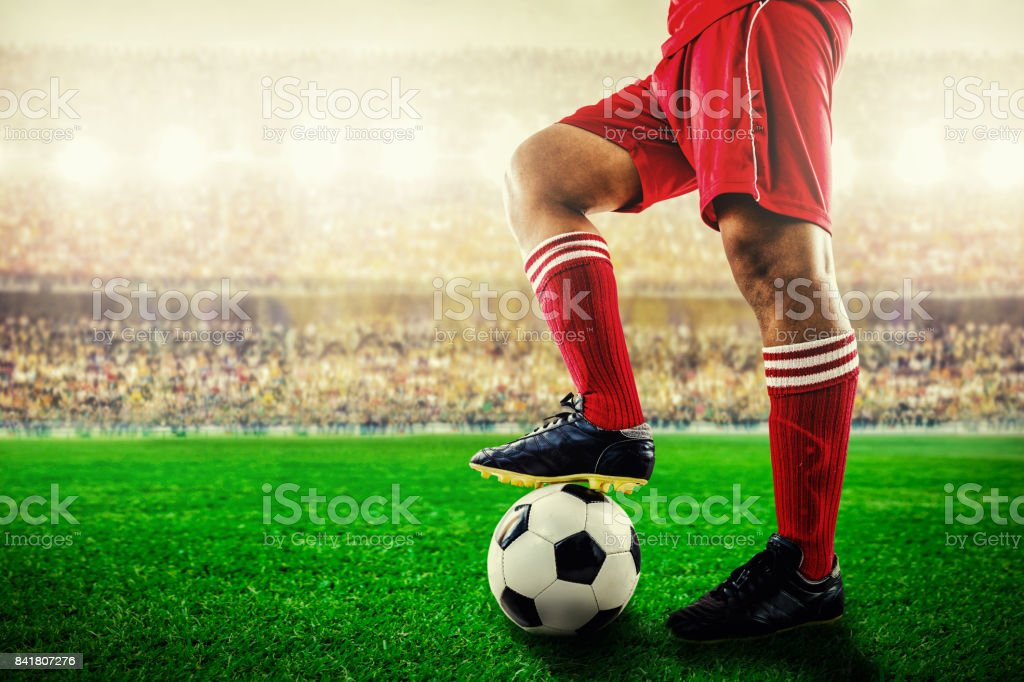 feet of red team football player on soccer ball for kick-off in the stadium stock photo