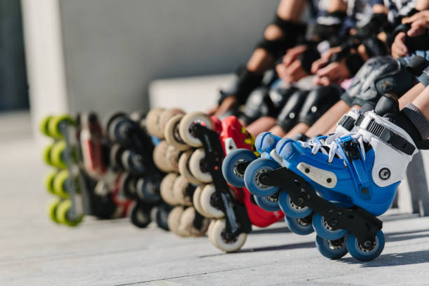 Feet of rollerbladers wearing inline roller skates sitting in outdoor skate park, Close up view of wheels befor skating stock photo