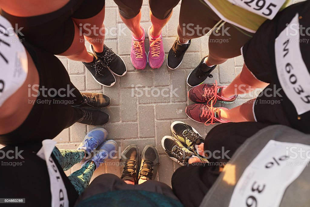 Feet of runners standing in a circle stock photo