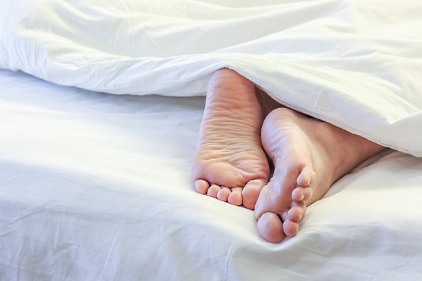 feet of sleeping woman in white bed room - saubere zehen stock-fotos und bilder