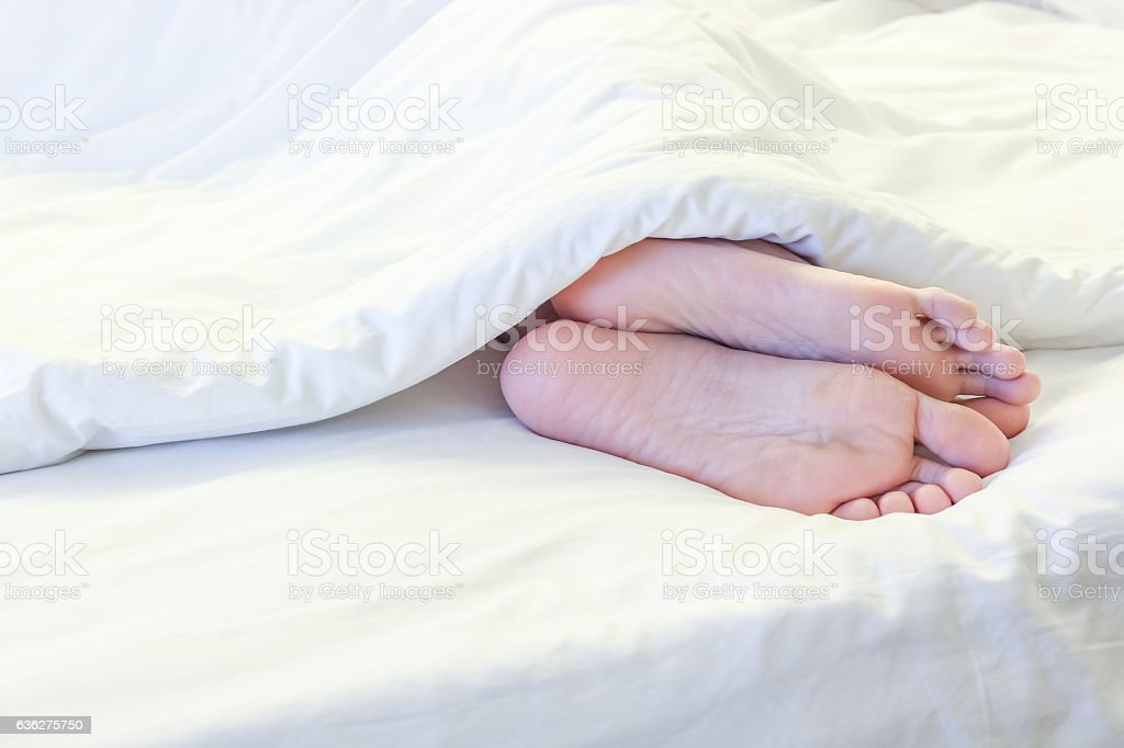 Feet Of Sleeping Woman In White Bed Room Stock Photo & More
