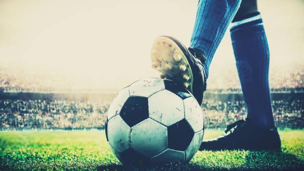 pisan de pies del jugador de fútbol en balón de fútbol para el kick-off en el estadio - foto de stock