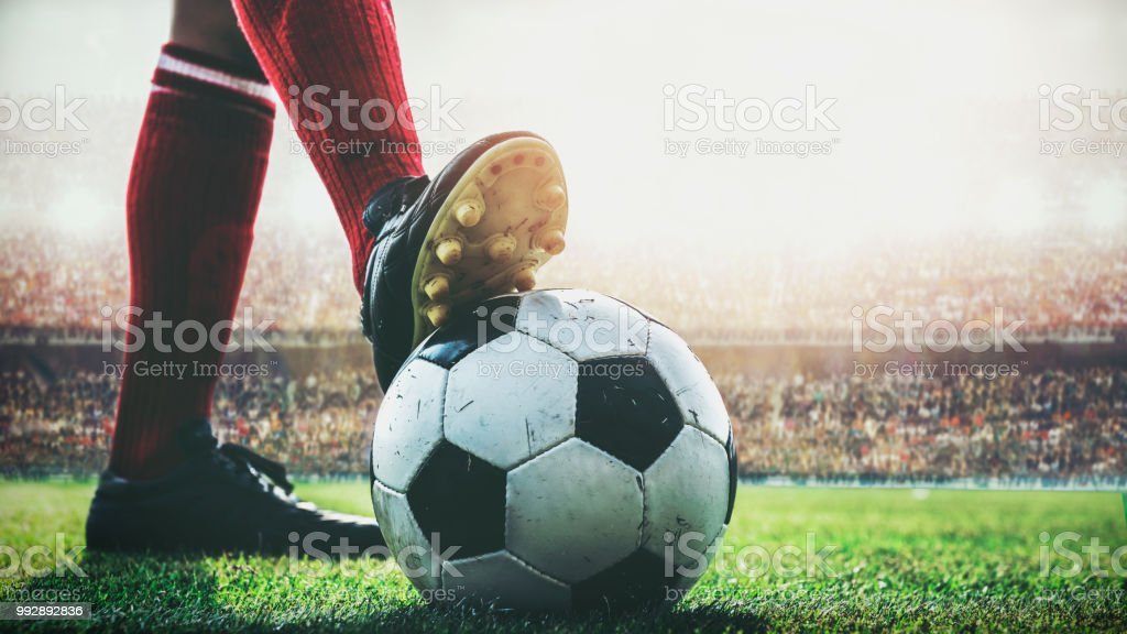 feet of soccer player tread on soccer ball for kick-off in the stadium stock photo