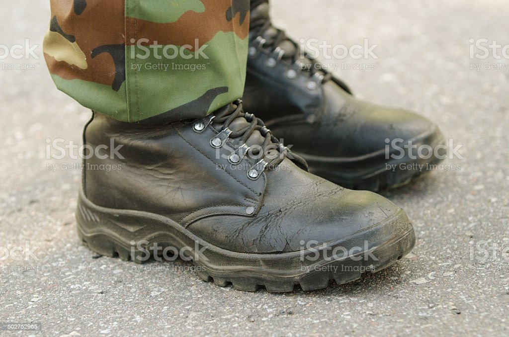 Feet of soldier in military boots and uniform stock photo