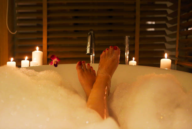 Feet of the young woman in bath with foam and candles stock photo