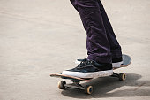Feet of unknown man on top of skateboard rolling inside bowl