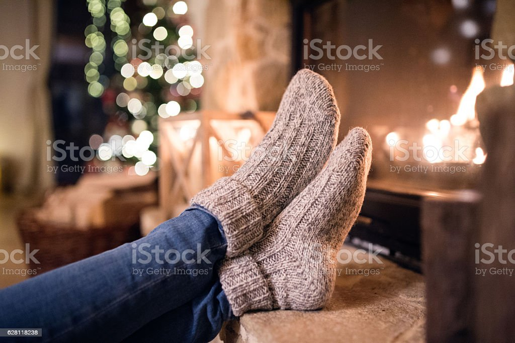 Feet of unrecognizable woman in socks by the Christmas fireplace stock photo