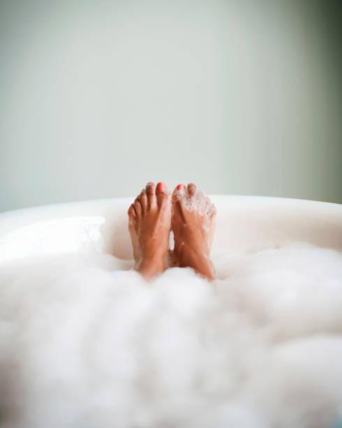 Feet of woman in bubble bath relaxing. stock photo