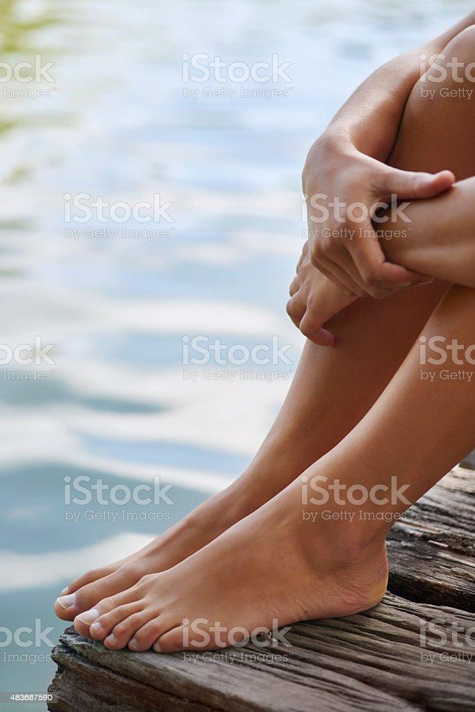 Feet of woman sitting near a pond stock photo