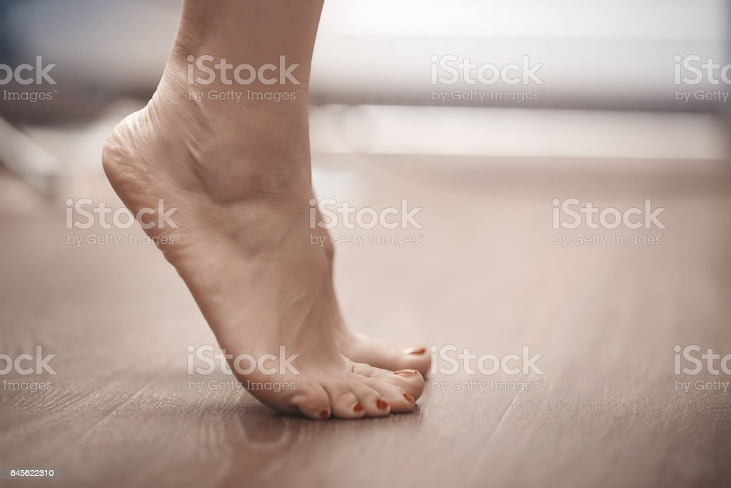 Feet of woman standing on tiptoe stock photo