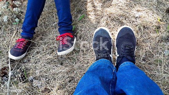 Feet of young lovers sitting next to sports shoes and jeans. The theme of love. Love relationship the boy and girl. Body parts of people on the background of forest soil.