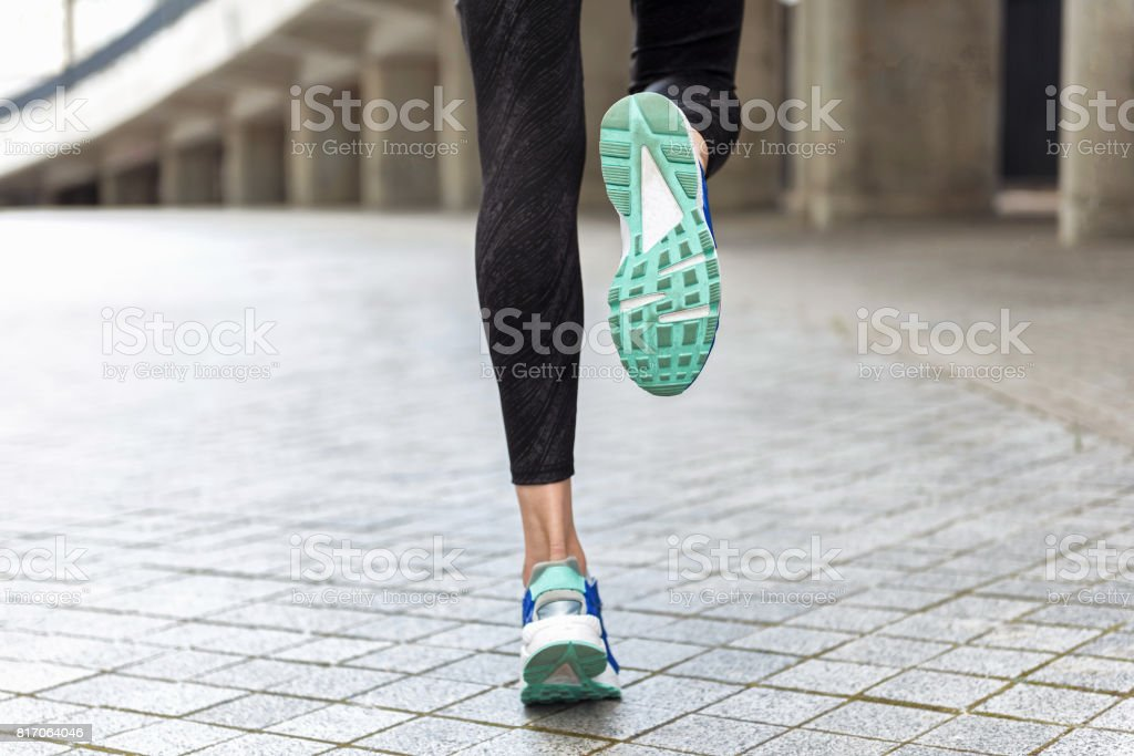 Feet of young woman jogging outside stock photo
