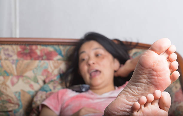 Feet of young woman lying on sofa and phoning stock photo