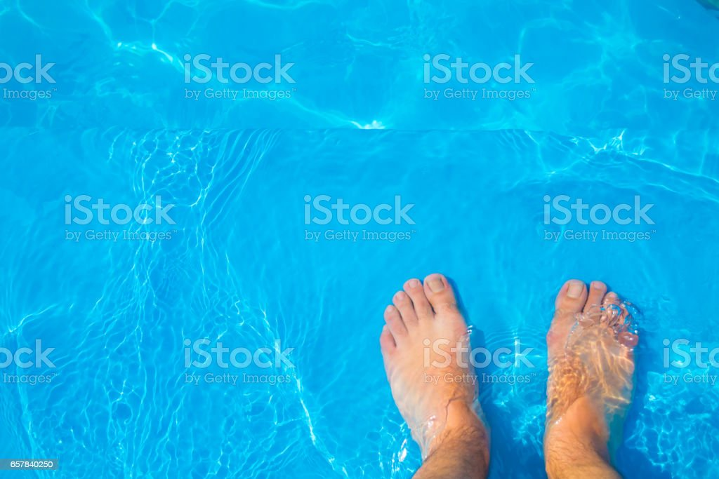 Feet on a pool stock photo
