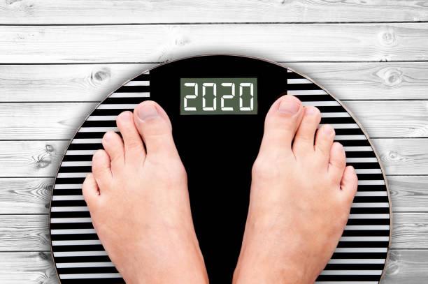 2020 Fuß auf einer Gewichtsskala auf weißen Brettern, Neujahr und Urlaub Ernährung und Ernährung Konzept – Foto