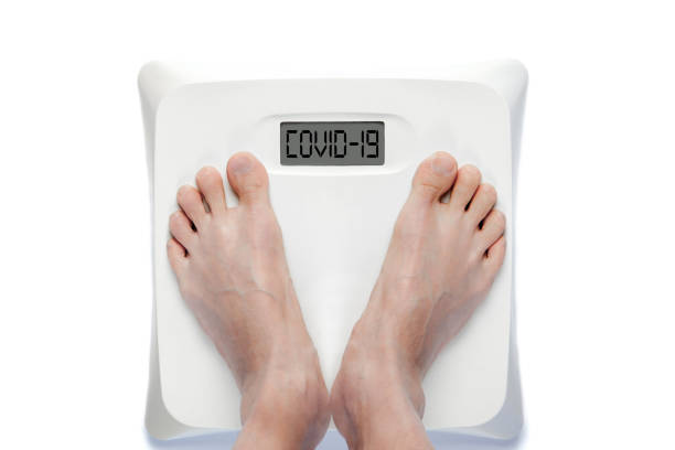 Feet on Bathroom Scale With COVID-19 Text Isolated on White Background stock photo