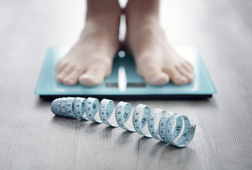 Feet on bathroom scale with measuring tape