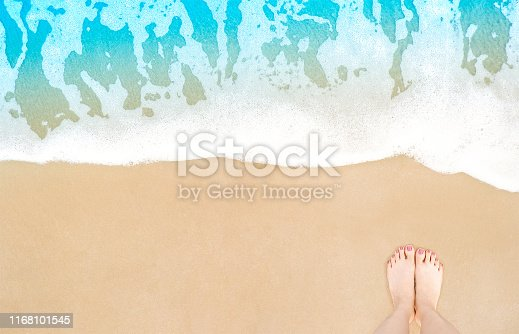 Feet on beach background. Top view on naked feet and legs in sand with wave motion coming to the foot - foaming sea texture. Summer and vacation holiday concept. Selfie barefoot woman standing ocean.