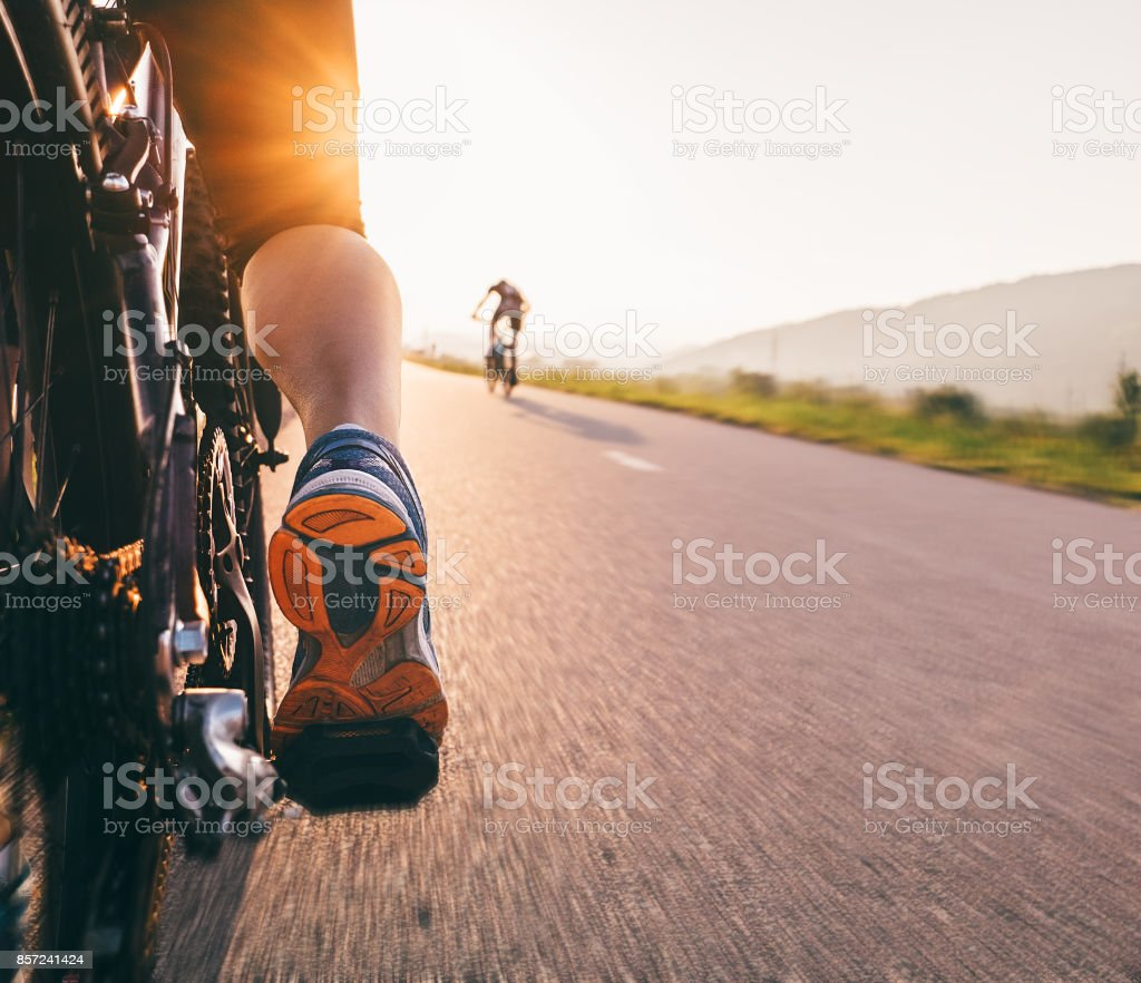 Feet on bycikle pedal in sunset light - close up image stock photo