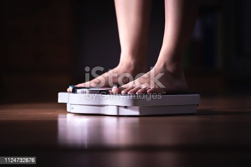 istock Feet on scale. Weight loss and diet concept. Woman weighing herself. Fitness lady dieting. Weightloss and dietetics. 1124732676