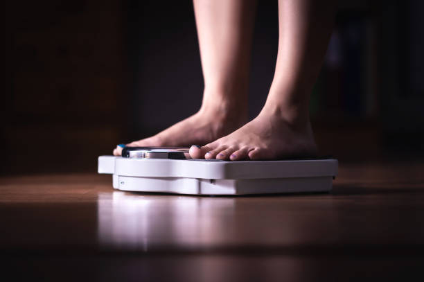 Feet on scale. Weight loss and diet concept. Woman weighing herself. Fitness lady dieting. Weightloss and dietetics. Feet on scale. Weight loss and diet concept. Woman weighing herself. Fitness lady dieting. Weightloss and dietetics. Dark late night mood. anorexia nervosa stock pictures, royalty-free photos & images