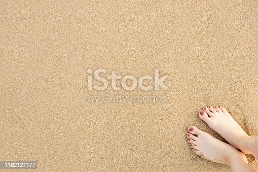 Feet on Sea Sand Beach Background. Top View. Closeup of Barefoot Woman Standing on Golden Sandy Beach in Sunny Summer Day. Selfie Foot and Brown Pedicure on Sand. Holiday and Vacation Concept.