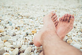 Male feet on a marble beach.