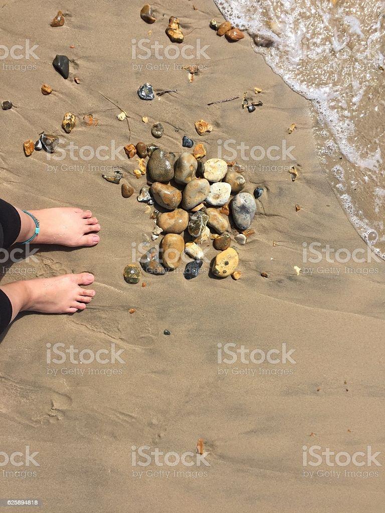 Feet on the beach with rocks stock photo