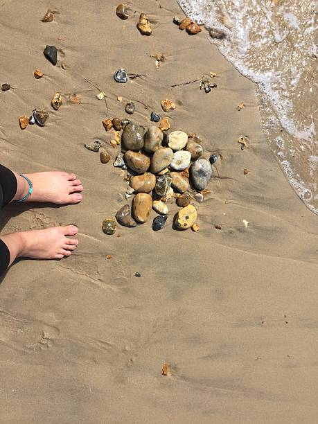 Feet on the beach with rocks stock photo