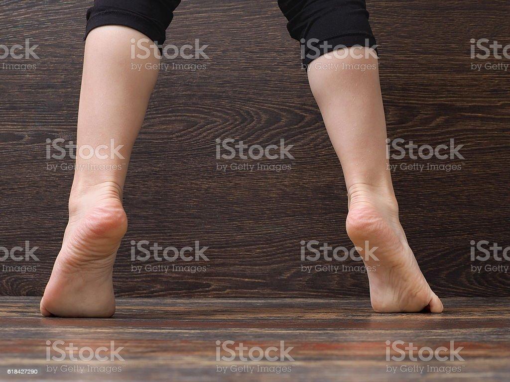 Feet on the floor of the child standing on tiptoe stock photo