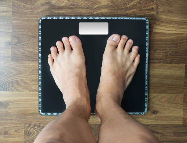Feet on Weighing scale, person's looking down view stock photo