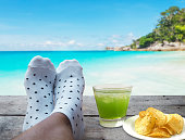 feet on wooden floor with glass of apple juice and potato chips over beach background, Relaxtion on vacation concept