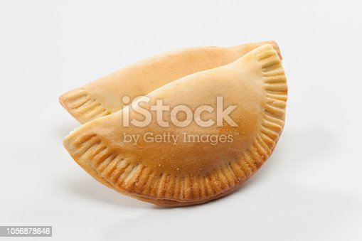Empanadas on white background. Studio shot. An empanada is a type of pasty baked or fried in many countries of the Americas and in Spain. Empanadas are made by folding dough over a stuffing, which may consist of meat, cheese or other ingredients.