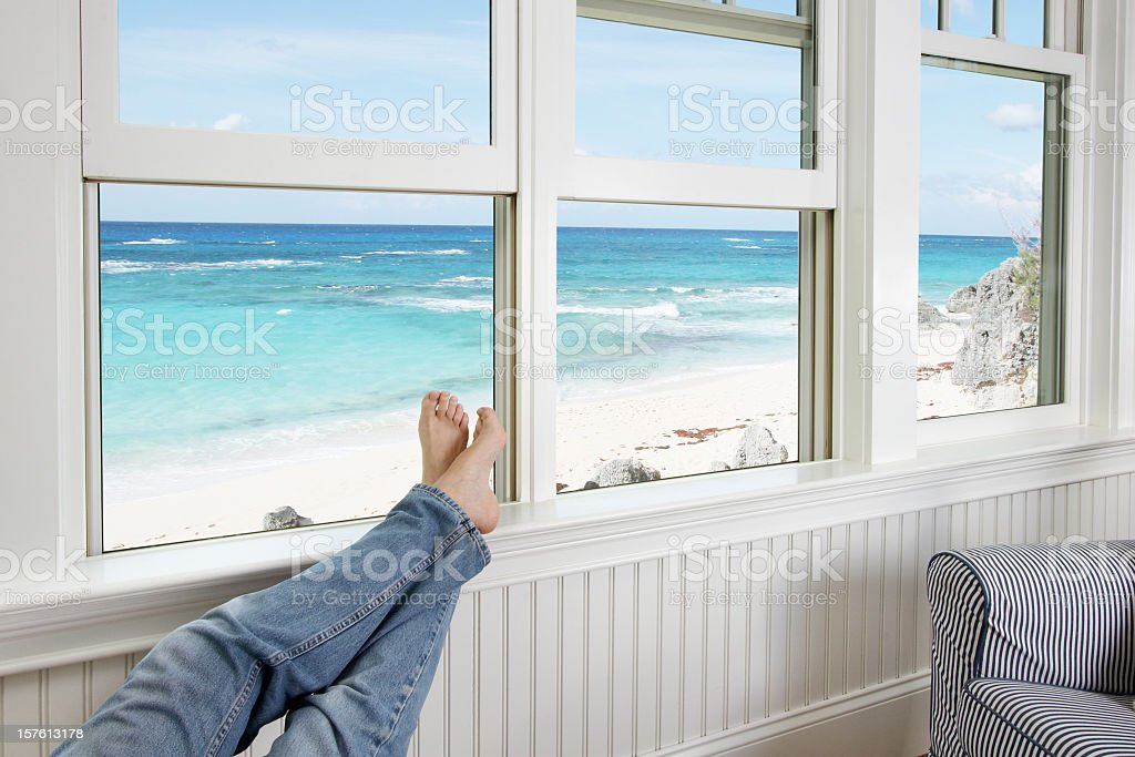 Feet resting on the sill of a window facing the beach stock photo