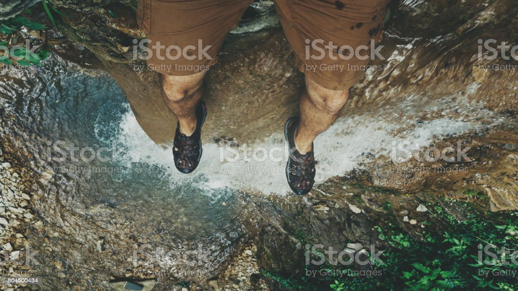 Feet selfie on cliff with waterfall view Travel Lifestyle adventure vacations concept stock photo