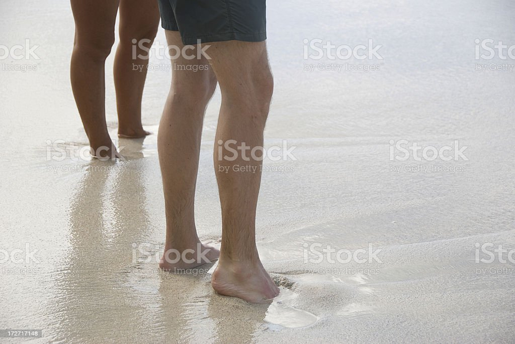 Feet Sink into Wet Sand stock photo