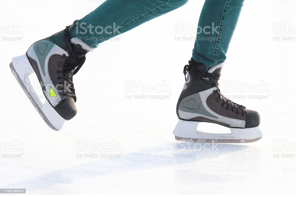 Feet skating on the ice rink. Hobbies and recreation. Sports and...