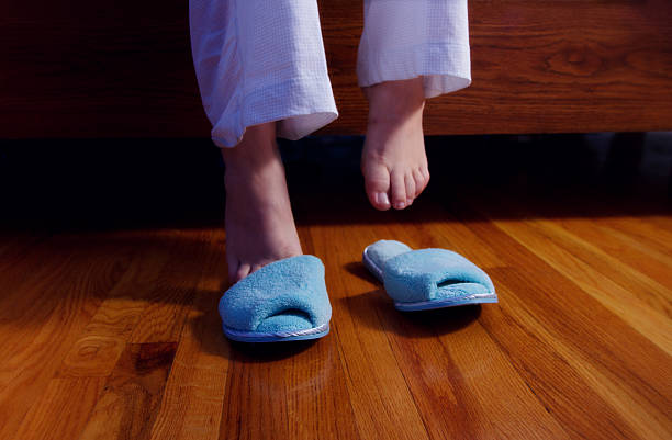 Feet Slipping Into Slippers In A Dark Bedroom stock photo