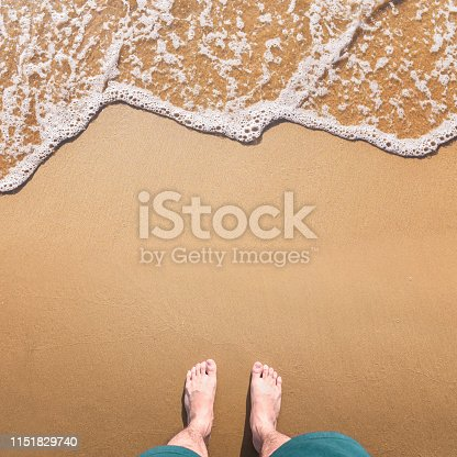1088451256 istock photo Feet stand on sea sand and wave with copy space, Vacation on ocean beach, Summer holiday. 1151829740