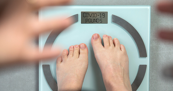 Feet standing on digital weight scale with the words COVID-19 Pounds written on, coronavirus and diet concept. top view crisis
