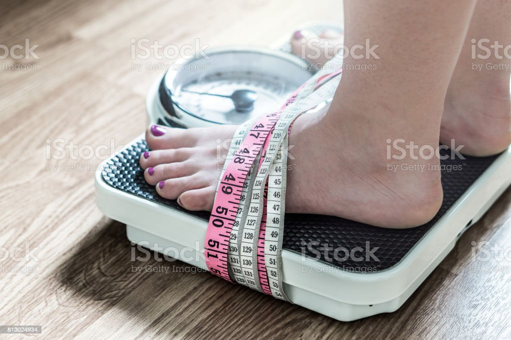 Feet tied up with measuring tape to a weight scale. Addiction and obsession to weight loss. Anorexia and eating disorder concept. stock photo
