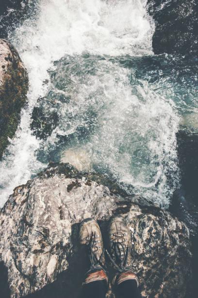 Füße, trekking Stiefel auf Stein auf Reisende allein im freien Wildbahn Lifestyle Reisen überleben Konzept Abenteuer Urlaub Top Aussicht auf den Fluss – Foto