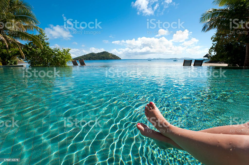 Feet up by the pool, relaxing in paradise royalty-free stock photo