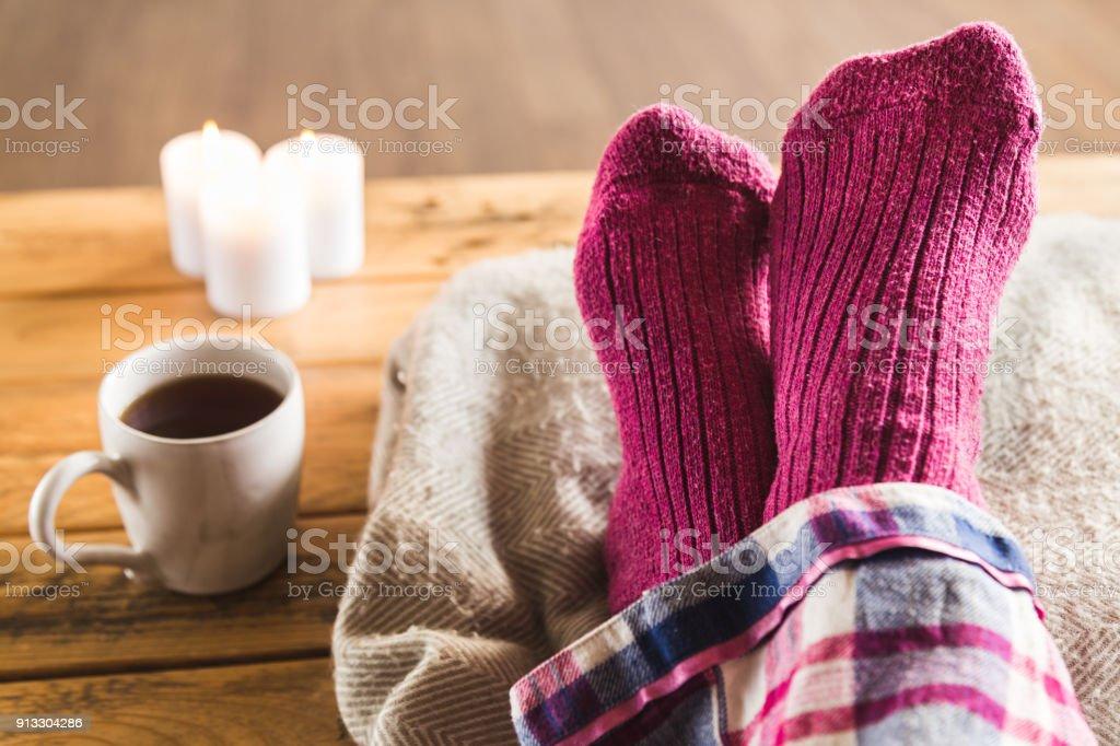 Füße hoch in gemütlichen wollig rosa Socken mit Tasse Tee und Kerzen – Foto