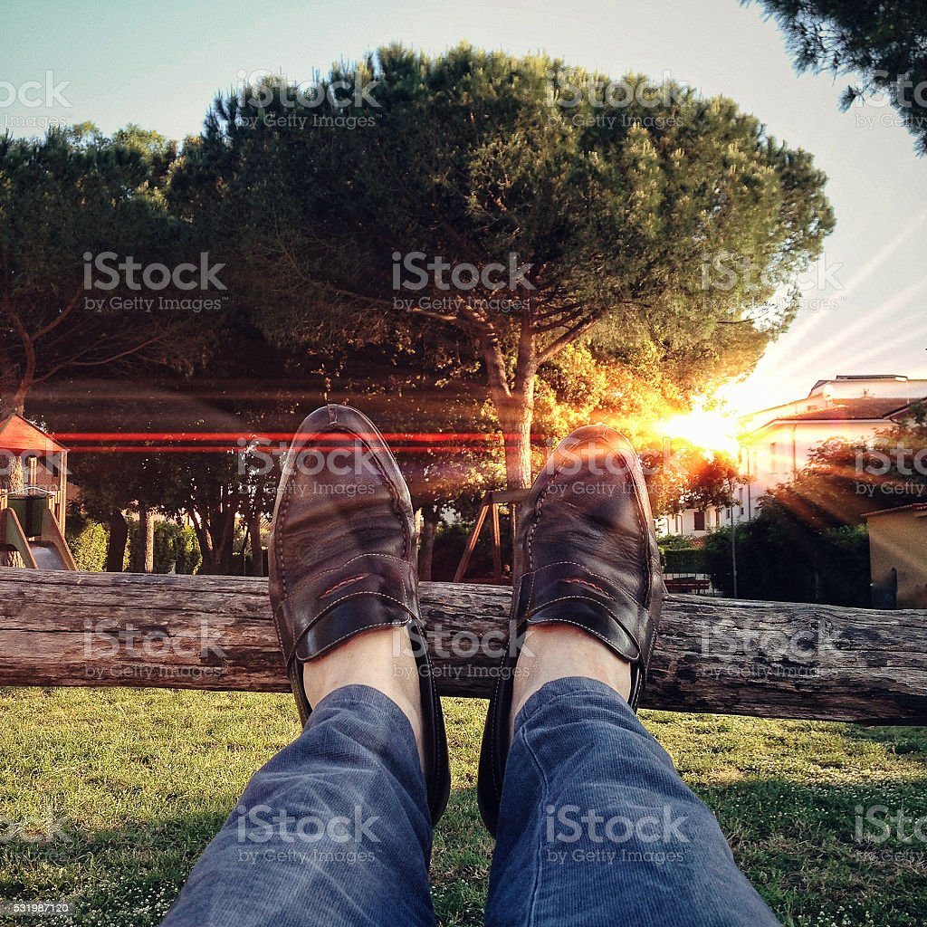 Feet up, wooden fence, outdoors, sunset stock photo