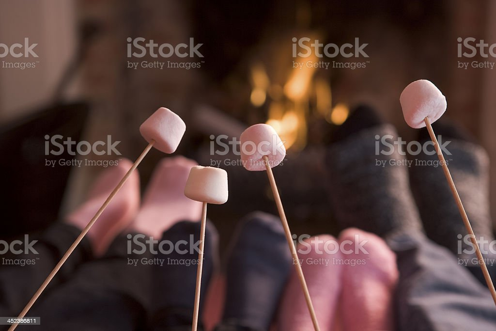 Feet warming at a fireplace with marshmallows on sticks stock photo