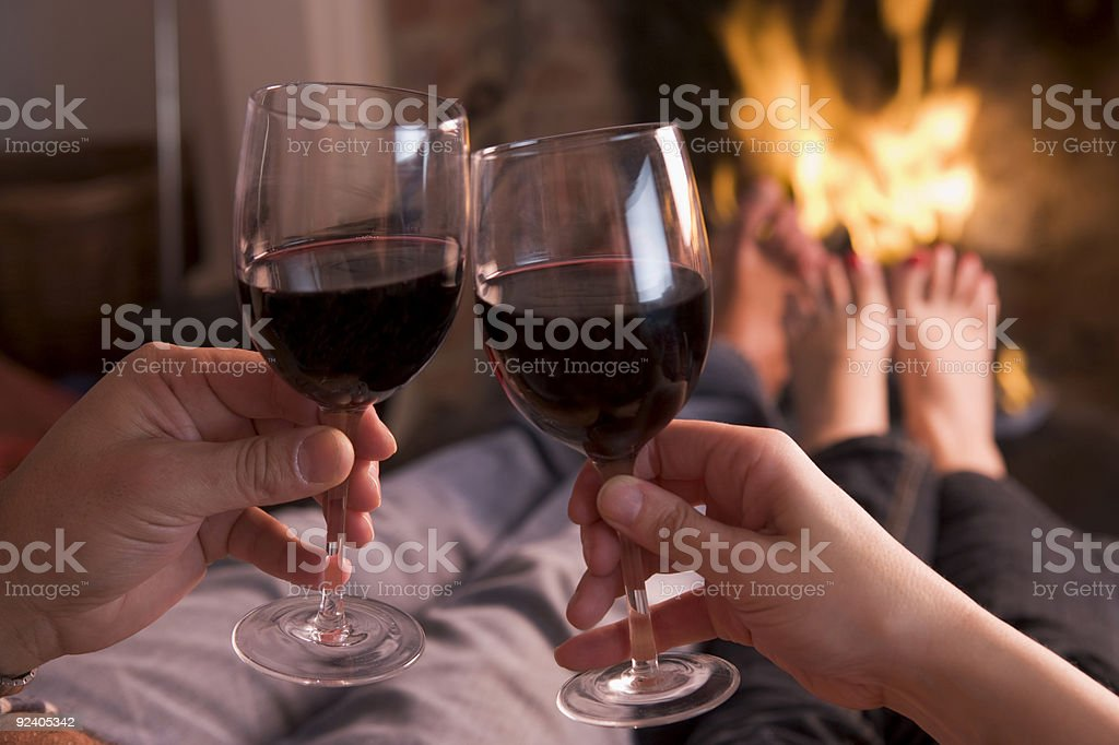 Feet warming at fireplace with hands holding wine stock photo