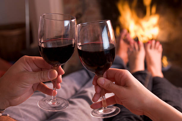 Feet warming at fireplace with hands holding wine  log fire stock pictures, royalty-free photos & images