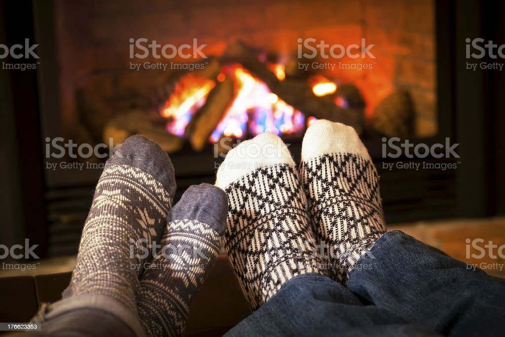 Feet warming by fireplace stock photo