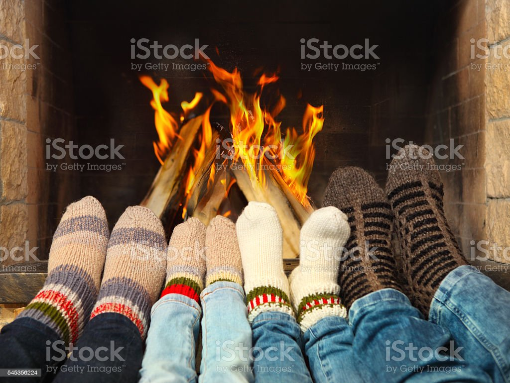 Feet warming near the fireplace stock photo